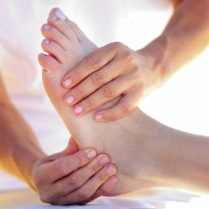 Hands holding foot for massage